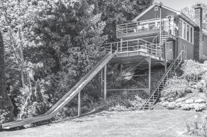 "Called 'The Slide House,' this two-level 2,800 sq. ft. home at 5403 Dallas Street in the village of Lexington was built in 1984 on a half-acre lot, which has a 24 ft. access to the broad sand beach on the north side of Lexington harbor. It has four bedrooms on the main floor, with two bonus bedrooms on the lower level. There are three baths and a second kitchen. The asking price is $450,000. It will be featured in the June 16 episode of the ""Beach House Hunters"" reality TV show."